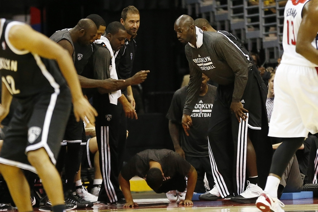 Oct 8, 2013; Washington, DC, USA; Brooklyn Nets point guard Deron Williams (middle) does push ups on the sidelines as teammates watch against the Washington Wizards in the fourth quarter at Verizon Center. The Nets won 111-106 in overtime. Mandatory Credit: Geoff Burke-USA TODAY Sports