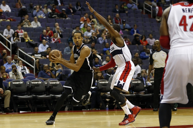 Oct 8, 2013; Washington, DC, USA; Brooklyn Nets point guard Shaun Livingston (14) dribbles the ball as Washington Wizards point guard John Wall (2) defends in the third quarter at Verizon Center. The Nets won 111-106 in overtime. Mandatory Credit: Geoff Burke-USA TODAY Sports
