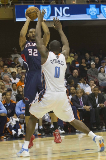 Oct 8, 2013; Asheville, NC, USA;  Atlanta Hawks power forward Mike Scott (32) shoots the ball over Charlotte Bobcats power forward Bismack Biyombo (0) during the second half at the U.S. Cellular Center.The Hawks defeated the Bobcats 87-85.  Mandatory Credit: Jeremy Brevard-USA TODAY Sports