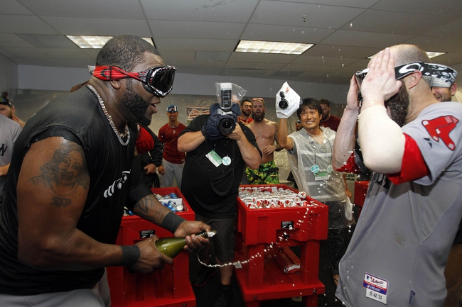 Oct 8, 2013; St. Petersburg, FL, USA; Boston Red Sox designated hitter David Ortiz (left) and Boston Red Sox second baseman Dustin Pedroia (right) celebrate in the locker room as they pour champagne on them as they beat the Tampa Bay Rays of game four of the American League divisional series at Tropicana Field. Boston Red Sox defeated theTampa Bay Rays 3-1. Mandatory Credit: Kim Klement-USA TODAY Sports