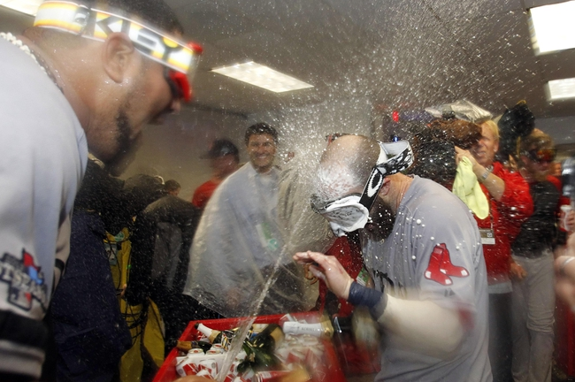 Oct 8, 2013; St. Petersburg, FL, USA; Boston Red Sox second baseman Dustin Pedroia (right) is sprayed with champagne as they celebrate beating the Tampa Bay Rays in game four of the American League divisional series at Tropicana Field. Boston Red Sox defeated theTampa Bay Rays 3-1. Mandatory Credit: Kim Klement-USA TODAY Sports