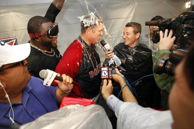 Oct 8, 2013; St. Petersburg, FL, USA; Boston Red Sox designated hitter David Ortiz (left) pours champagne on manager John Farrell (center) as he gets interviewed after they beat the Tampa Bay Rays of game four of the American League divisional series at Tropicana Field. Boston Red Sox defeated theTampa Bay Rays 3-1. Mandatory Credit: Kim Klement-USA TODAY Sports