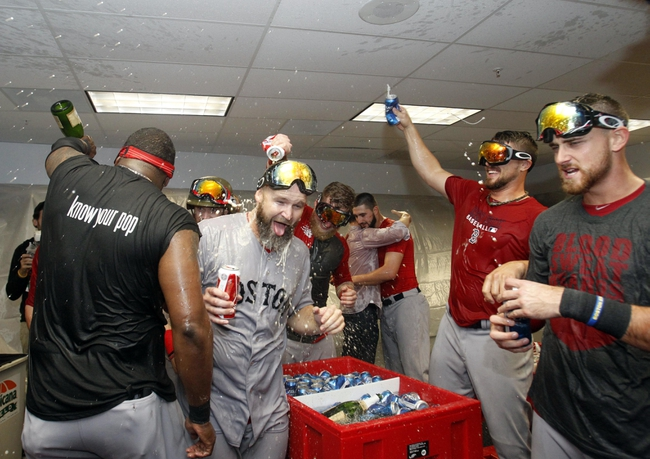 Oct 8, 2013; St. Petersburg, FL, USA; Boston Red Sox catcher David Ross (center) and teammates celebrate in the locker room as they pour champagne on them as they beat the Tampa Bay Rays of game four of the American League divisional series at Tropicana Field. Boston Red Sox defeated theTampa Bay Rays 3-1. Mandatory Credit: Kim Klement-USA TODAY Sports