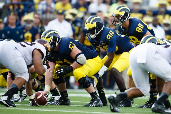Oct 5, 2013; Ann Arbor, MI, USA; Michigan Wolverines quarterback Devin Gardner (98) gets set to run a play against the Minnesota Golden Gophers at Michigan Stadium. Mandatory Credit: Rick Osentoski-USA TODAY Sports
