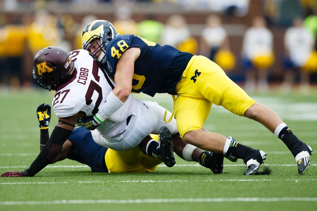 Oct 5, 2013; Ann Arbor, MI, USA; Minnesota Golden Gophers running back David Cobb (27) is tackled by Michigan Wolverines linebacker Desmond Morgan (48) at Michigan Stadium. Mandatory Credit: Rick Osentoski-USA TODAY Sports