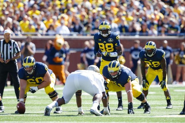 Sep 14, 2013; Ann Arbor, MI, USA; Michigan Wolverines quarterback Devin Gardner (98) gets set to run a play against the Akron Zips at Michigan Stadium. Mandatory Credit: Rick Osentoski-USA TODAY Sports