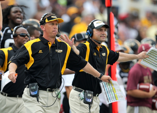 Aug 31, 2013; Hattiesburg, MS, USA; Southern Miss Golden Eagles head coach Todd Monken, left, and assistant John Wozniak on the sidelines against the Texas State Bobcats at M.M. Roberts Stadium. Mandatory Credit: Chuck Cook-USA TODAY Sports