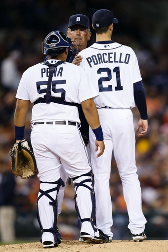 Sep 21, 2013; Detroit, MI, USA; Detroit Tigers pitching coach Jeff Jones (51) talks to catcher Brayan Pena (55) and starting pitcher Rick Porcello (21) against the Chicago White Sox at Comerica Park. Mandatory Credit: Rick Osentoski-USA TODAY Sports