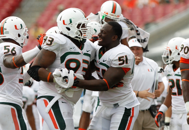 Sep 28, 2013; Tampa, FL, USA; Miami Hurricanes defensive lineman Luther Robinson (93) and defensive lineman Shayon Green (51) celebrate against the South Florida Bulls during the second half at Raymond James Stadium. Miami Hurricanes defeated the South Florida Bulls 49-21. Mandatory Credit: Kim Klement-USA TODAY Sports