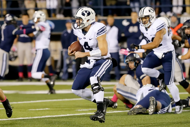 Oct 4, 2013; Logan, UT, USA; Brigham Young Cougars quarterback Taysom Hill (4) runs the ball against the Utah State Aggies in the third quarter at Romney Stadium.  Brigham Young Cougars defeated the Utah State Aggies 31-14.  Mandatory Credit: Chris Nicoll-USA TODAY Sports