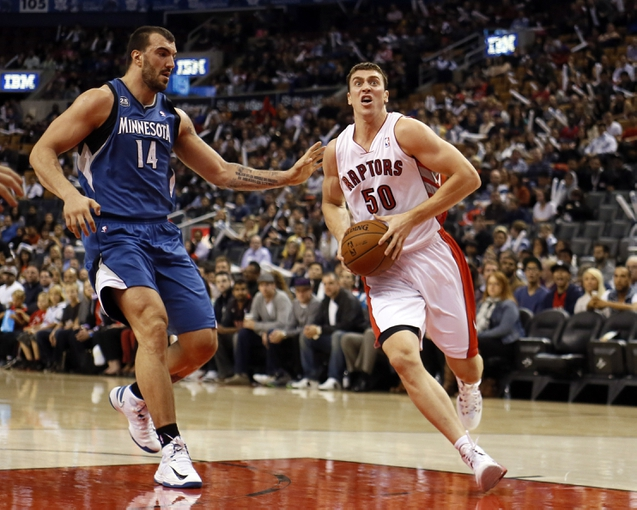 Oct 9, 2013; Toronto, Ontario, CAN; Toronto Raptors forward Tyler Hansbrough (50) drives to the net against Minnesota Timberwolves center Nikola Pekovic (14) during the first half at the Air Canada Centre. Mandatory Credit: John E. Sokolowski-USA TODAY Sports