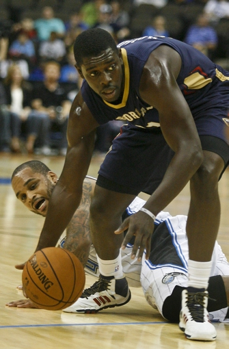 Oct 9, 2013; Jacksonville, FL, USA; Orlando Magic guard Jameer Nelson (bottom) defends against New Orleans Pelicans guard Jrue Holiday (11) in the first quarter of their game at Jacksonville Veterans Memorial Arena. Mandatory Credit: Phil Sears-USA TODAY Sports