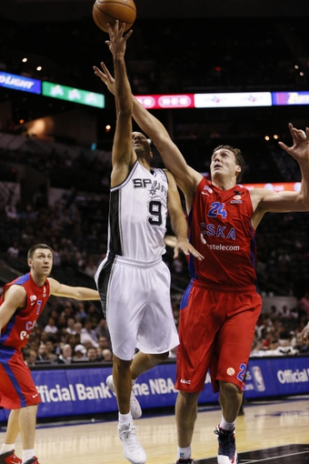 Oct 9, 2013; San Antonio, TX, USA; San Antonio Spurs guard Tony Parker (9) drives to the basket as CSKA Moscow center Sasha Kaun (24) defends during the first half at the AT&T Center. Mandatory Credit: Soobum Im-USA TODAY Sports