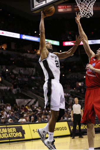 Oct 9, 2013; San Antonio, TX, USA; San Antonio Spurs forward Tim Duncan (21) dunks against CSKA Moscow center Sasha Kaun (right) during the first half at the AT&T Center. Mandatory Credit: Soobum Im-USA TODAY Sports