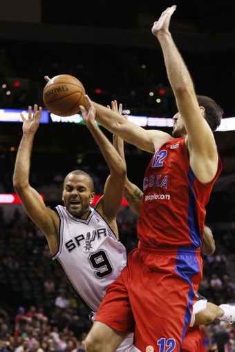 Oct 9, 2013; San Antonio, TX, USA; San Antonio Spurs guard Tony Parker (9) gets fouled while shooting against CSKA Moscow guard Aaron Jackson (not pictured) during the first half at the AT&T Center. Mandatory Credit: Soobum Im-USA TODAY Sports