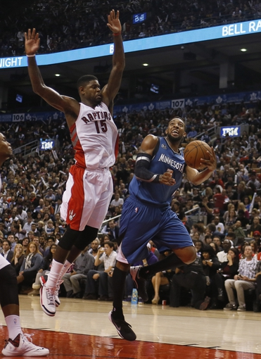 Oct 9, 2013; Toronto, Ontario, CAN; Toronto Raptors center-forward Amir Johnson (15) defends against Minnesota Timberwolves forward Derrick Williams (7) at the Air Canada Centre. Minnesota defeated Toronto 101-89. Mandatory Credit: John E. Sokolowski-USA TODAY Sports
