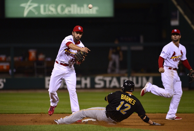Oct 9, 2013; St. Louis, MO, USA; St. Louis Cardinals second baseman Matt Carpenter (13) turns a double play against Pittsburgh Pirates shortstop Clint Barmes (12) during the sixth inning in game five of the National League divisional series playoff baseball game at Busch Stadium. Mandatory Credit: Scott Rovak-USA TODAY Sports
