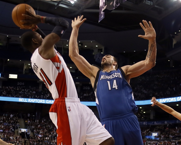 Oct 9, 2013; Toronto, Ontario, CAN; Minnesota Timberwolves center Nikola Pekovic (14) goes to block a shot by Toronto Raptors guard Terrence Ross (31) at the Air Canada Centre. Minnesota defeated Toronto 101-89. Mandatory Credit: John E. Sokolowski-USA TODAY Sports