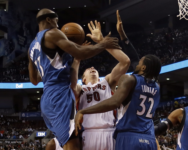 Oct 9, 2013; Toronto, Ontario, CAN; Minnesota Timberwolves forward Dante Cunningham (33) and Minnesota Timberwolves center Ronny Turiaf (32) defend against Toronto Raptors forward Tyler Hansbrough (50) at the Air Canada Centre. Minnesota defeated Toronto 101-89. Mandatory Credit: John E. Sokolowski-USA TODAY Sports