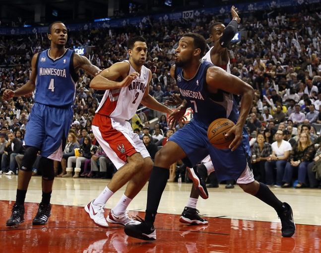 Oct 9, 2013; Toronto, Ontario, CAN; Minnesota Timberwolves forward Derrick Williams (7) drives to the net as guard Lorenzo Brown (4) and Toronto Raptors guard Landry Fields (2) look on at the Air Canada Centre. Minnesota defeated Toronto 101-89. Mandatory Credit: John E. Sokolowski-USA TODAY Sports