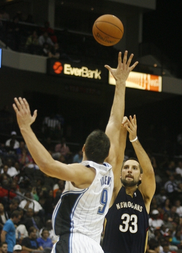 Oct 9, 2013; Jacksonville, FL, USA; New Orleans Pelicans forward Ryan Anderson (33) shoots over Orlando Magic center Nikola Vucevic (9) in the second half of their game at Jacksonville Veterans Memorial Arena. The New Orleans Pelicans beat the Orlando Magic 99-95. Mandatory Credit: Phil Sears-USA TODAY Sports