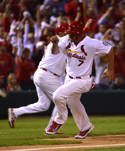 Oct 9, 2013; St. Louis, MO, USA; St. Louis Cardinals left fielder Matt Holliday (7) scores against the Pittsburgh Pirates during the sixth inning in game five of the National League divisional series playoff baseball game at Busch Stadium. Mandatory Credit: Scott Rovak-USA TODAY Sports