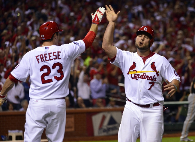 Oct 9, 2013; St. Louis, MO, USA; St. Louis Cardinals left fielder Matt Holliday (7) celebrates scoring with third baseman David Freese (23) during the sixth inning against the Pittsburgh Pirates in game five of the National League divisional series playoff baseball game at Busch Stadium. Mandatory Credit: Scott Rovak-USA TODAY Sports