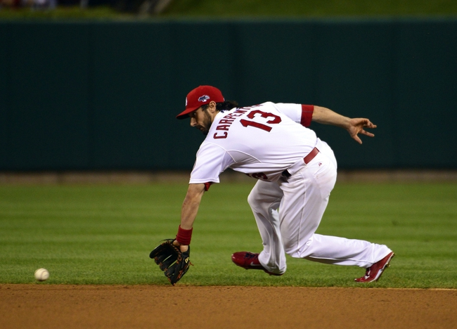 Oct 9, 2013; St. Louis, MO, USA; St. Louis Cardinals second baseman Matt Carpenter (13) fields a ground ball against the Pittsburgh Pirates in game five of the National League divisional series playoff baseball game at Busch Stadium. Mandatory Credit: Scott Rovak-USA TODAY Sports