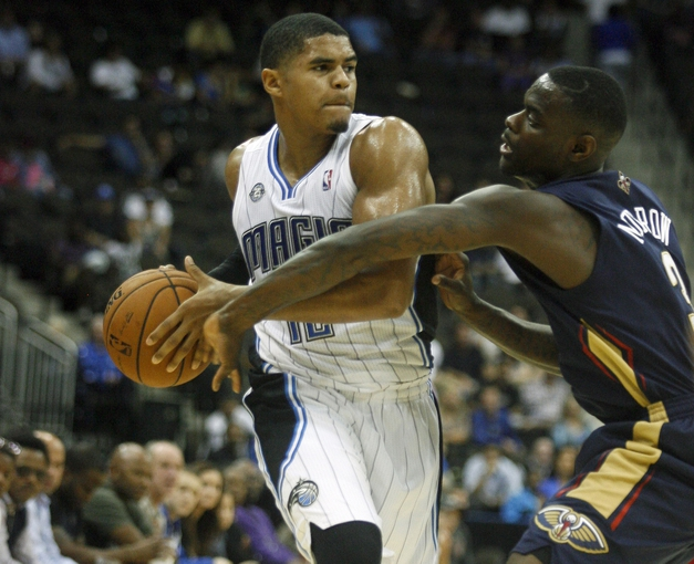 Oct 9, 2013; Jacksonville, FL, USA; Orlando Magic forward Tobias Harris (12) keeps the ball away from New Orleans Pelicans guard Anthony Morrow (3) in the second half of their game at Jacksonville Veterans Memorial Arena. The New Orleans Pelicans beat the Orlando Magic 99-95. Mandatory Credit: Phil Sears-USA TODAY Sports