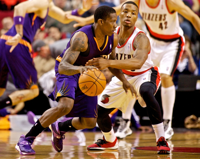 Oct 9, 2013; Portland, OR, USA; Phoenix Suns point guard Eric Bledsoe (2) drives past Portland Trail Blazers point guard Damian Lillard (0) in the first quarter at the Moda Center. Mandatory Credit: Craig Mitchelldyer-USA TODAY Sports