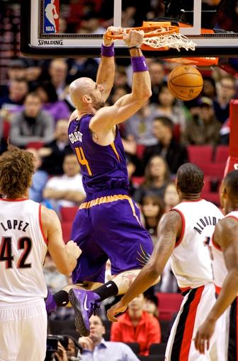 Oct 9, 2013; Portland, OR, USA; Phoenix Suns center Marcin Gortat (4) dunks over Portland Trail Blazers center LaMarcus Aldridge (12) in the first quarter at the Moda Center. Mandatory Credit: Craig Mitchelldyer-USA TODAY Sports