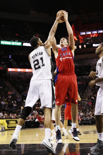 Oct 9, 2013; San Antonio, TX, USA; CSKA Moscow center Sasha Kaun (24) has his shot blocked by San Antonio Spurs forward Tim Duncan (21) during the second half at the AT&T Center. The Spurs won 95-93 in overtime. Mandatory Credit: Soobum Im-USA TODAY Sports
