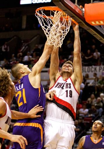 Oct 9, 2013; Portland, OR, USA; Portland Trail Blazers power forward Joel Freeland (19) dunks over Phoenix Suns center Alex Len (21) at the Moda Center. Mandatory Credit: Craig Mitchelldyer-USA TODAY Sports