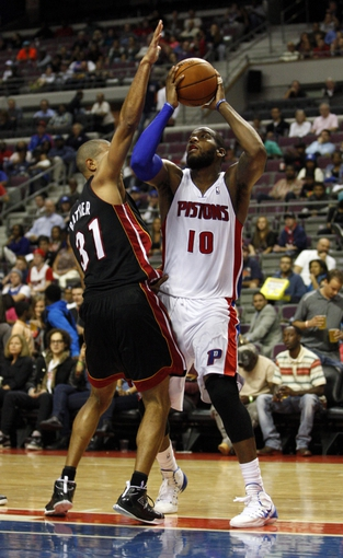 Oct 10, 2013; Auburn Hills, MI, USA; Detroit Pistons center Greg Monroe (10) defended by Miami Heat small forward Shane Battier (31) during the third quarter at The Palace of Auburn Hills. Heat beat the Pistons 112-107. Mandatory Credit: Raj Mehta-USA TODAY Sports