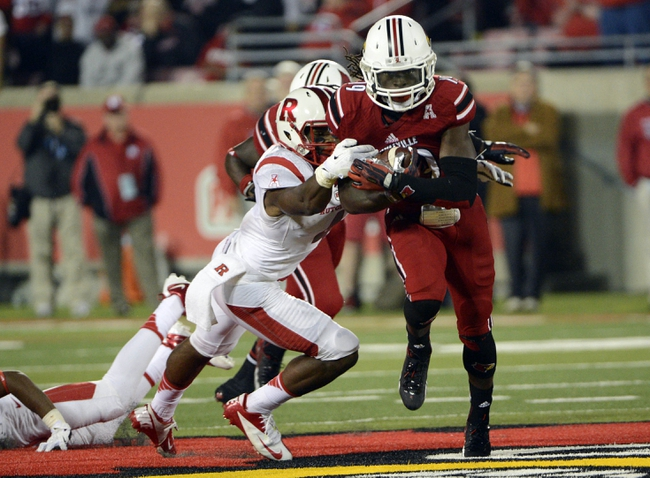 Oct 10, 2013; Louisville, KY, USA; Louisville Cardinals cornerback Terell Floyd (19) returns an interception past Rutgers Scarlet Knights wide receiver Leonte Carroo (4) during the second half at Papa John's Cardinal Stadium. Louisville defeated Rutgers 24-10.  Mandatory Credit: Jamie Rhodes-USA TODAY Sports