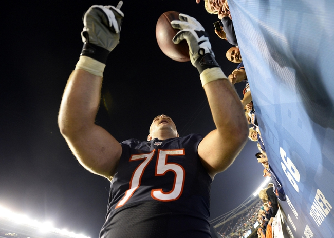 Oct 10, 2013; Chicago, IL, USA; Chicago Bears offensive guard Kyle Long (75) signs an autograph for a fan after the game against the New York Giants at Soldier Field. Chicago defeats New York 27-21. Mandatory Credit: Mike DiNovo-USA TODAY Sports