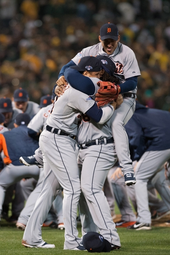 Oct 10, 2013; Oakland, CA, USA; Detroit Tigers designated hitter Victor Martinez ( left) and first baseman Prince Fielder (middle) and shortstop Jose Iglesias (top) celebrate on the field after defeating the Oakland Athletics 3-0 in game five of the American League divisional series playoff baseball game at O.co Coliseum. Mandatory Credit: Ed Szczepanski-USA TODAY Sports