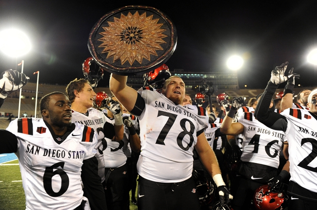 Oct 10, 2013; Colorado Springs, CO, USA; San Diego State Aztecs offensive linesman Bryce Quigley (78) holds up a shield following the win over the Air Force Falcons at Falcon Stadium. The Aztecs defeated the Falcons 27-20. Mandatory Credit: Ron Chenoy-USA TODAY Sports