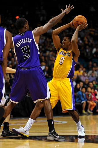 Oct 10, 2013; Las Vegas, NV, USA; Los Angeles Lakers guard Nick Young (0) looks to pass the ball while being defended against by Sacramento Kings forward Patrick Patterson (9) during an NBA preseason game at MGM Grand Arena. Mandatory Credit: Stephen R. Sylvanie-USA TODAY Sports