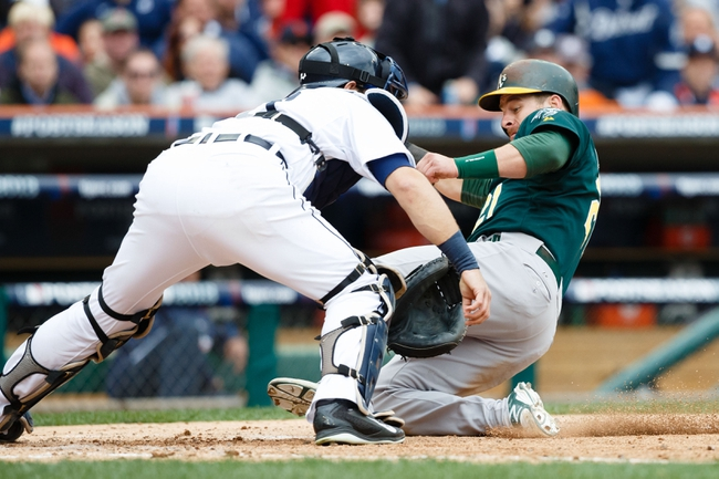 Oct 7, 2013; Detroit, MI, USA; Oakland Athletics catcher Stephen Vogt (21) slides in to home safe as Detroit Tigers catcher Alex Avila (13) waits for the ball in the fourth inning in game three of the American League divisional series playoff baseball game at Comerica Park. Mandatory Credit: Rick Osentoski-USA TODAY Sports