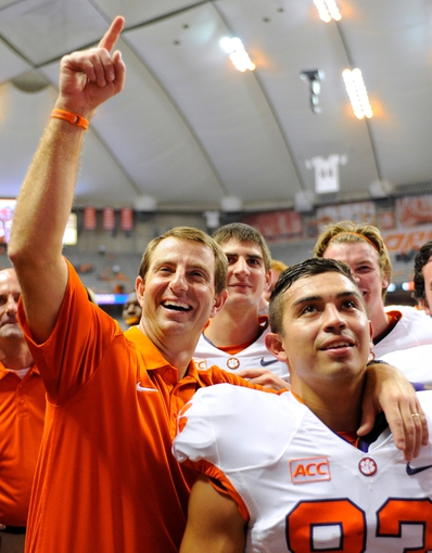 Oct 5, 2013; Syracuse, NY, USA; Clemson Tigers head coach Dabo Swinney (left) reacts to the crowd following the game against the Syracuse Orange at the Carrier Dome.  Clemson defeated Syracuse 49-14.  Mandatory Credit: Rich Barnes-USA TODAY Sports