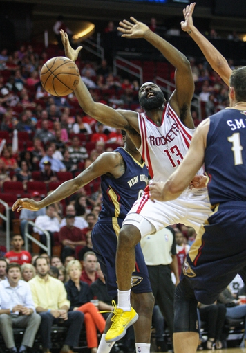 Oct 5, 2013; Houston, TX, USA; Houston Rockets shooting guard James Harden (13) attempts to get control of a loose ball during the third quarter against the New Orleans Pelicans at Toyota Center. The Pelicans defeated the Rockets 116-115. Mandatory Credit: Troy Taormina-USA TODAY Sports