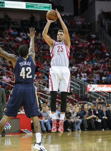 Oct 5, 2013; Houston, TX, USA; Houston Rockets small forward Chandler Parsons (25) shoots during the third quarter as New Orleans Pelicans small forward Lance Thomas (42) defends at Toyota Center. Mandatory Credit: Troy Taormina-USA TODAY Sports