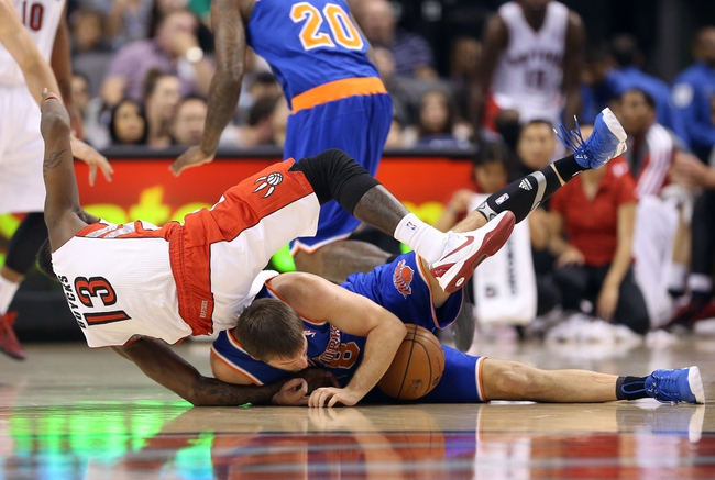 Oct 11, 2013; Toronto, Ontario, CAN; Toronto Raptors point guard Dwight Buycks (13) falls over New York Knicks point guard Beno Udrih (18) who holds on to the ball at Air Canada Centre. The Raptors beat the Knicks 100-91. Mandatory Credit: Tom Szczerbowski-USA TODAY Sports