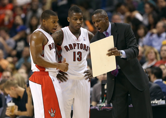 Oct 11, 2013; Toronto, Ontario, CAN; Toronto Raptors head coach Dwane Casey gives instructions to point guard Kyle Lowry (7) and point guard Dwight Buycks (13) against the New York Knicks at Air Canada Centre. The Raptors beat the Knicks 100-91. Mandatory Credit: Tom Szczerbowski-USA TODAY Sports