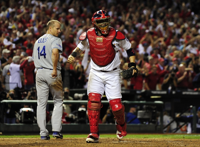 Oct 11, 2013; St. Louis, MO, USA; St. Louis Cardinals catcher Yadier Molina (right) reacts after tagging out Los Angeles Dodgers second baseman Mark Ellis (14) at home plate in the 10th inning in game one of the National League Championship Series baseball game at Busch Stadium. Mandatory Credit: Scott Rovak-USA TODAY Sports
