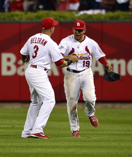 Oct 11, 2013; St. Louis, MO, USA; St. Louis Cardinals right fielder Carlos Beltran (3) is congratulated by center fielder Jon Jay (19) after throwing out Los Angeles Dodgers second baseman Mark Ellis (not pictured) at home plate in the 10th inning in game one of the National League Championship Series baseball game at Busch Stadium. Mandatory Credit: Scott Rovak-USA TODAY Sports