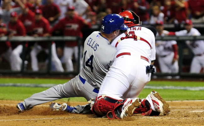 Oct 11, 2013; St. Louis, MO, USA; Los Angeles Dodgers second baseman Mark Ellis (left) is tagged out at home plate by St. Louis Cardinals catcher Yadier Molina (4) during the 10th inning in game one of the National League Championship Series baseball game at Busch Stadium. Mandatory Credit: Jeff Curry-USA TODAY Sports