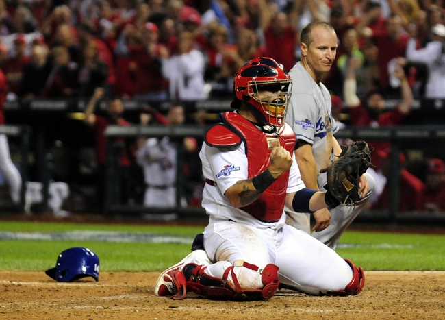 Oct 11, 2013; St. Louis, MO, USA; St. Louis Cardinals catcher Yadier Molina (front) reacts after tagging out Los Angeles Dodgers second baseman Mark Ellis (rear) at home plate in the 10th inning in game one of the National League Championship Series baseball game at Busch Stadium. Mandatory Credit: Jeff Curry-USA TODAY Sports