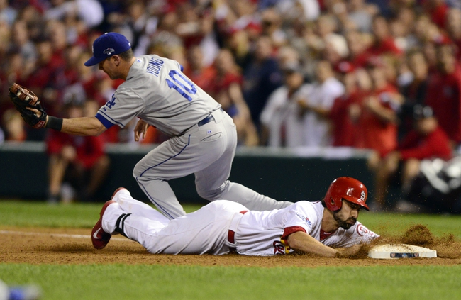 Oct 11, 2013; St. Louis, MO, USA; St. Louis Cardinals second baseman Matt Carpenter (bottom) dives back to first base ahead of the throw to Los Angeles Dodgers infielder Michael Young (10) during the 11th inning in game one of the National League Championship Series baseball game at Busch Stadium. Mandatory Credit: Jeff Curry-USA TODAY Sports